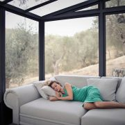 Woman-Sleeping-on-Couch-in-a-Sunroom